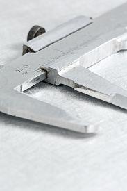 stock photo of vernier-caliper  - Stainless steel vernier caliper on scratched metal background - JPG