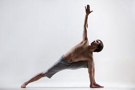 stock photo of revolver  - Sporty muscular young man working out yoga pilates fitness training doing lunge exercise Revolved Side Angle Pose Parivrtta Parsvakonasana gray background low key shot - JPG