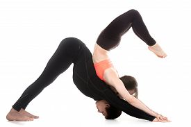 foto of scorpion  - Acro yoga two sporty people practice yoga in pair couple doing stretching exercise for spine scorpion and downward facing dog posture white background - JPG