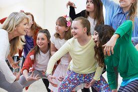 stock photo of teachers  - Group Of Children With Teacher Enjoying Drama Class Together - JPG