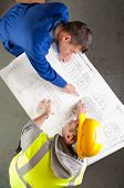 Builders Talk About Blueprint On Bench