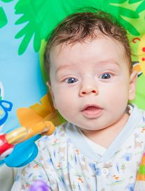 foto of playmate  - 3 months old baby boy playing and learning on the playmat - JPG