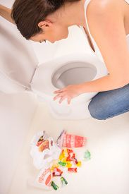 foto of vomiting  - Young woman vomiting into the toilet bowl in the early stages of pregnancy or after a night of partying and drinking - JPG