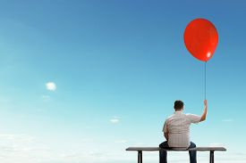 pic of sitting a bench  - Fat man sitting on bench with his back with balloon in hand - JPG