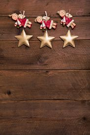 pic of christmas angel  - Three red and golden Christmas angels on old wooden background for a greeting card - JPG