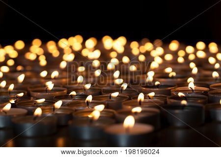 poster of Flaming candles. Spiritual image of tealights providing sacred light. Romantic candlelight at night. A spread of lit wax candles against black background with copy space.