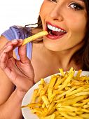 Woman eating french fries. Portrait of student consume fast food on table. Girl trying to eat junk.  poster