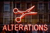 Red neon sign of the word 'Alterations' and a scissors icon, on a black background.