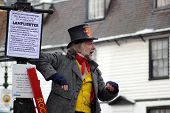 ROCHESTER CITY, KENT ,ENGLAND - DEC 11: Unidentified actor in top hat up a ladder plays part of lamp