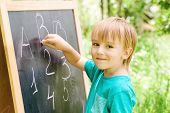 Cute Little Boy At Blackboard Practicing Counting And Math Outdoor. poster