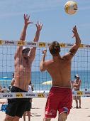 MANHATTAN BEACH, CA. - JULY 18: Mike Placek spikes the ball and Austin Rester attempts to block him