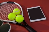 High angle view of sports shoes and digital tablet by balls on tennis racket over maroon background poster