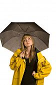 A pretty young woman in a raincoat and holding an umbrella checks to see if it is raining (isolated