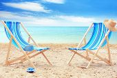 Pair of beach chairs at sea shore. Vacation concept poster