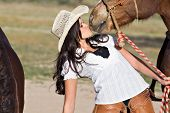 A young woman in chaps and a cowboy hat kisses her horse