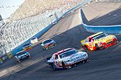 AVONDALE, AZ - APRIL 10: A.J. Allmendinger (#43) and Kevin Harvick (#29) lead a group of cars into t