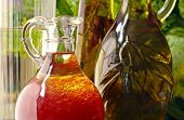 Sunlit still life of raspberry vinaigrette salad dressing in glass cruet with bottles of olive oil a