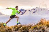 Trail runner man running on New Zealand mountains nature. Sport athlete jumping over hills with moun poster