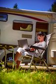 Woman looking at the laptop near the camping . Caravan car Vacation. Family vacation travel, holiday poster