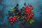 Assorted fresh berries with leaves on metal background. Mix of fresh berries with leaves on textured poster