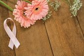 High angle view of pink Breast Cancer Awareness ribbon by gerbera flowers on wooden table poster