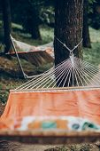 Comfortable Orange Hammock Hanging Outdoors In A Park, Boho Hammock Tied To Trees, Camping Concept poster