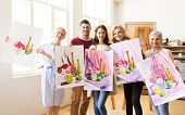 painting, education and people concept - group of artists or students holding still life pictures at poster