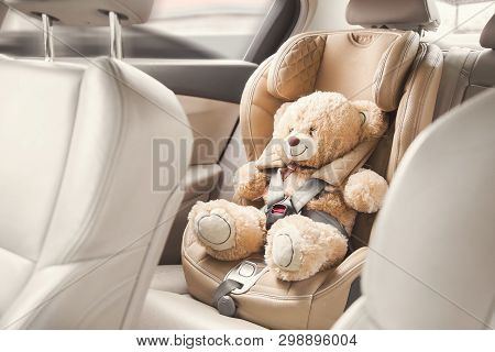 poster of Baby Child Seat Car. A Beige Teddy Bear Is Fastened With Seat Belts In A Car Seat. Travel By Car