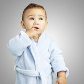 portrait of adorable infant with his finger in his mouth wearing a bathrobe over a grey background