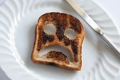 Sad and unhappy smiley made from toasted bread with knife and plate