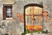Old brick wall with metal rusty gate and small window in town of La Morra, Northern Italy.