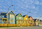 stock photo of white vinyl fence  - Street of new affordable houses - JPG