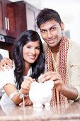 picture of indian money  - beautiful indian couple putting coins in piggybank - JPG
