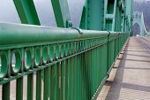 Green Railing perspective on St. Johns Bridge with view of one of the towers in soft background