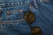 Round Sun Glasses On A Denim Texture Background. Round Yellow Glasses In The Front Pocket Of Jeans.  poster