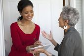 image of soliciting  - Black woman signs a petition at her front door - JPG