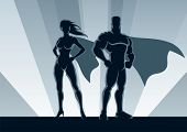 stock photo of hero  - Male and female superheroes, posing in front of a light.
