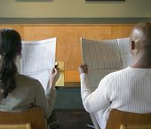 Rear view of businesspeople reading newspaper