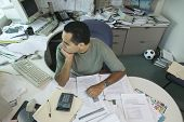 foto of idealistic  - Businessman sitting at messy desk - JPG