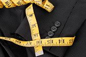 pic of tailoring  - Suit Tailoring concept with measuring tape around the sleeve of a business suit - JPG