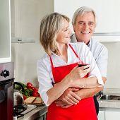 leitende manmade umarmen lächelnde Frau in Küche