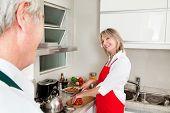 happy senior Woman Vorbereitung Abendessen in Küche lächelnd