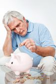 Worried senior man saving Euro money in piggy bank