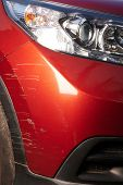 Scratched Paint On Red  Modern Car Bumper Close Up View poster