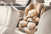 Baby Child Seat Car. A Beige Teddy Bear Is Fastened With Seat Belts In A Car Seat. Travel By Car poster