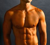 stock photo of pectorals  - Athletic shirtless male with tanned skin and rippled muscles - JPG