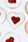 linzer homemade cookies with heart shape raspberry jam window, on white wooden backdrop