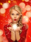 lovely woman in red dress blowing magic on the palms of her hands