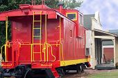 stock photo of caboose  - Antique red and yellow train caboose sittling at old railroad station