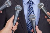 stock photo of politician  - Press conference with media microphones held in front of business man - JPG